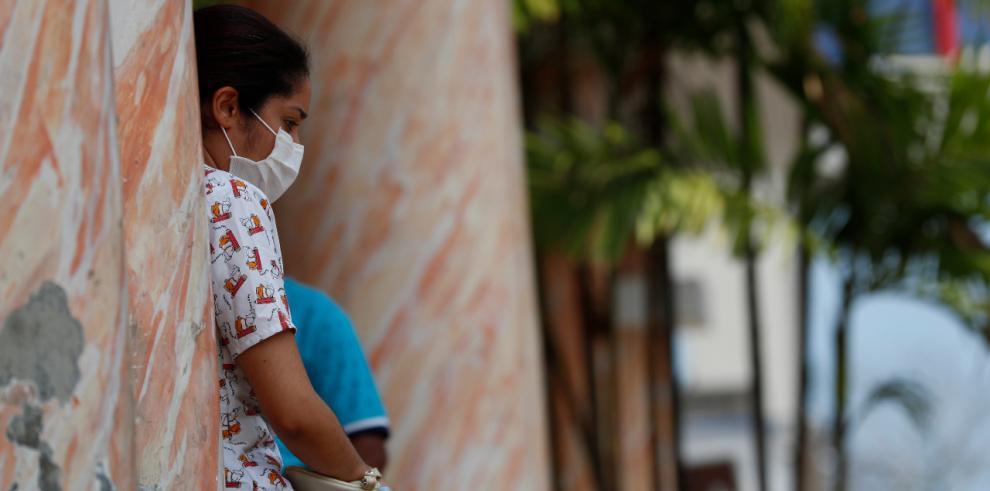 Una mujer descansa frente al Hospital Santo Tomas.