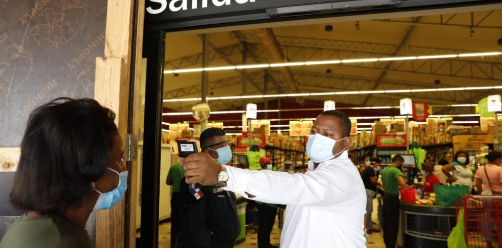 Una persona le toma la temperatura una ciudadana que intenta ingresar a  un supermercado.