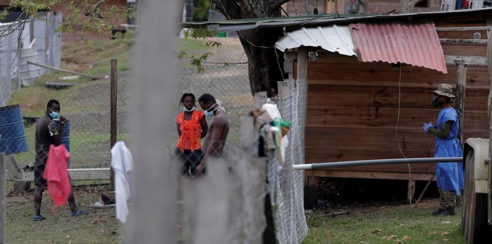 Migrantes hablan con un agente del Servicio Nacional de Fronteras de Panamá (Senafront), este viernes en la comunidad de Lajas Blancas, en Darién (Panamá).