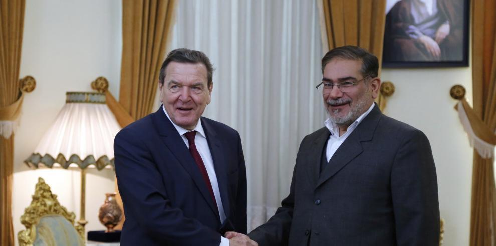 El secretario del Consejo Supremo de Seguridad Nacional iraní, Alí Shamjaní (d), estrecha la mano del excanciller alemán Gerhard Schröeder durante una reunión en Teherán (Irán)