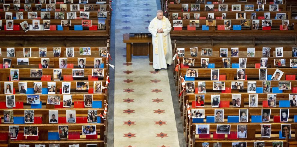 El abad Vincent Marville camina junto a los retratos en los bancos de la iglesia de los 400 feligreses
