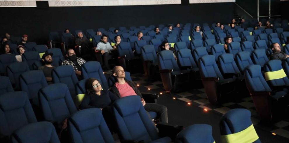 Grupos de personas con tapabocas asisten al cine, en San José