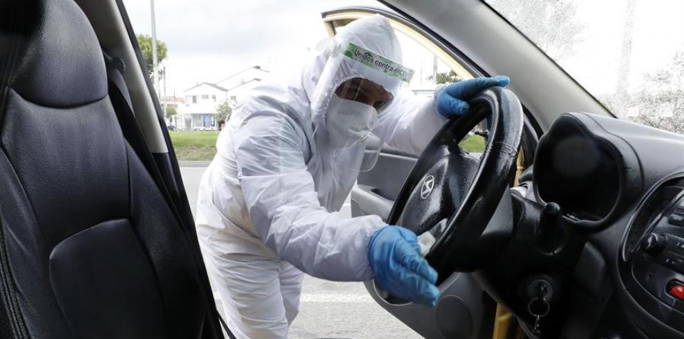 Un hombre desinfecta un taxi
