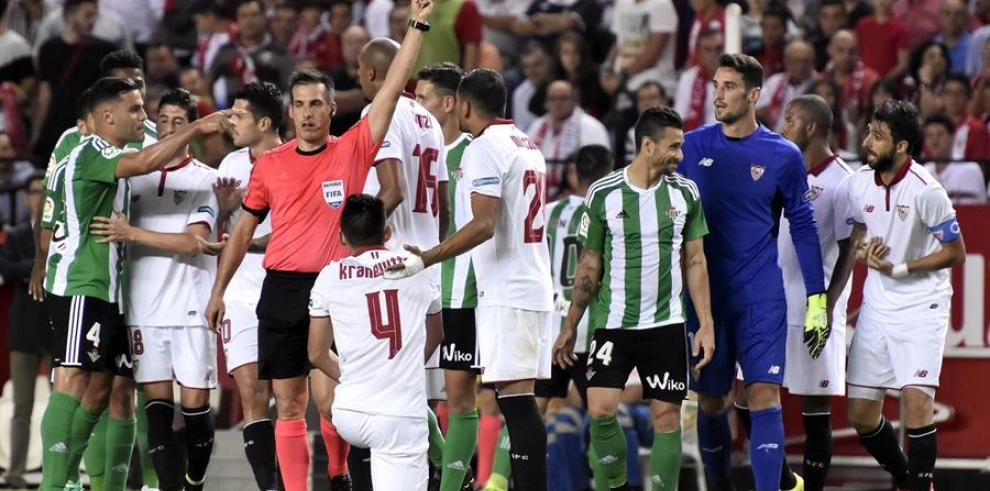 El árbitro Xavier Estrada saca tres tarjetas amarillas en un derbi sevillano en el estadio Sánchez Pizjuán, en Sevilla.