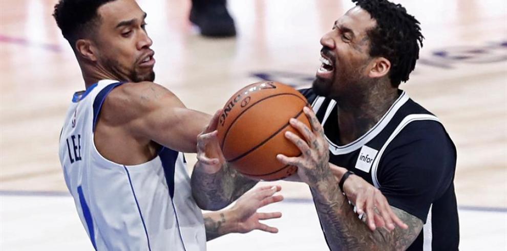Wilson Chandler, alero de los Nets de Brooklyn (d) pelea un balón con Dallas Mavericks player Courtney Lee (i) durante un partido de la NBA.