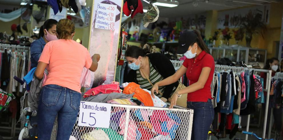 Un grupo de mujeres realiza compras en una tienda de ropa usada