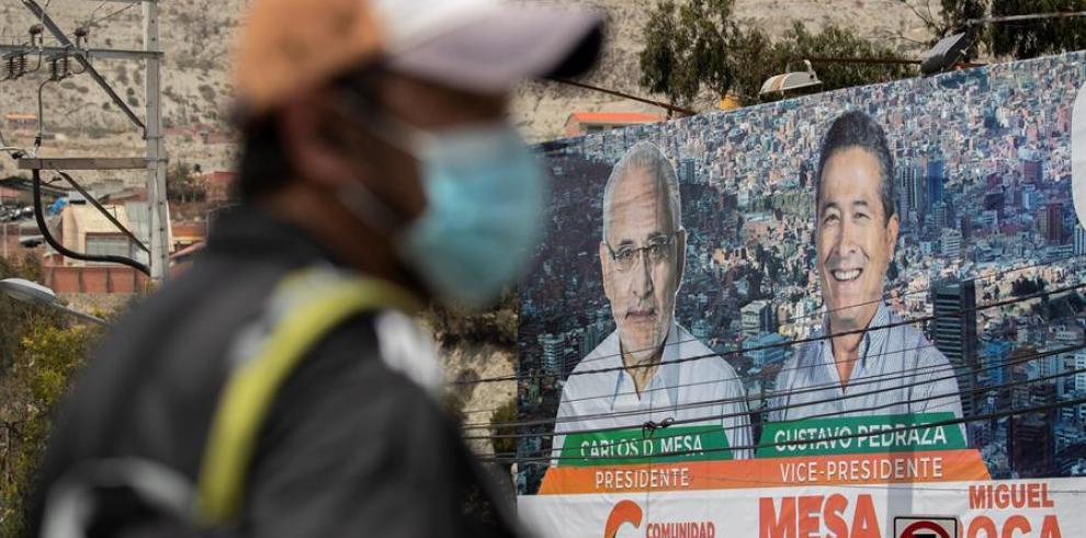 Un hombre pasa por un cartel que muestra al candidato a la presidencia Carlos Mesa, hoy en La Paz (Bolivia).