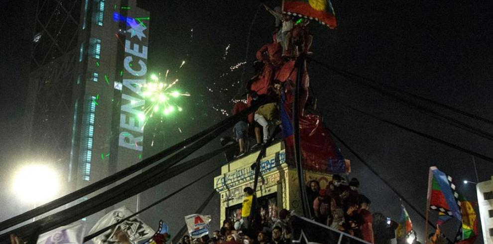 Decenas de personas celebran luego de conocer los resultados parciales del plebiscito constitucional, que apuntan al triunfo por una nueva Carta Magna hoy, en Santiago (Chile).