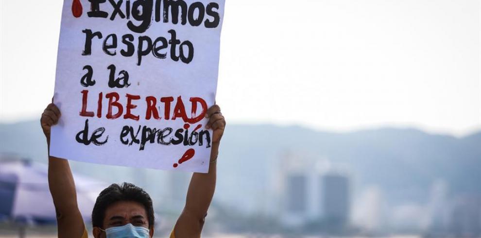 Un periodista mexicano sostiene un cartel en una protesta para exigir seguridad ante amenazas de crimen organizado, en Acapulco