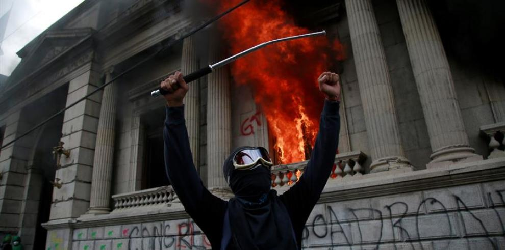 Un hombre protesta en frente del Congreso de Guatemala en llamas ocasionado por manifestantes que protestan contra del Gobierno del presidente, Alejandro Giammattei