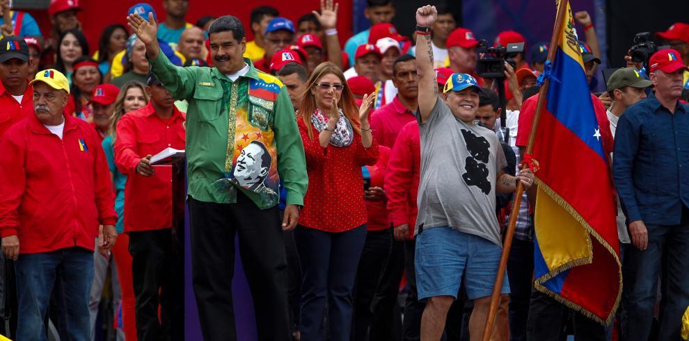 El presidente venezolano, Nicolás Maduro (i), saluda junto a la primera dama, Cilia Flores (c), y al exfutbolista argentino Diego Maradona (d)