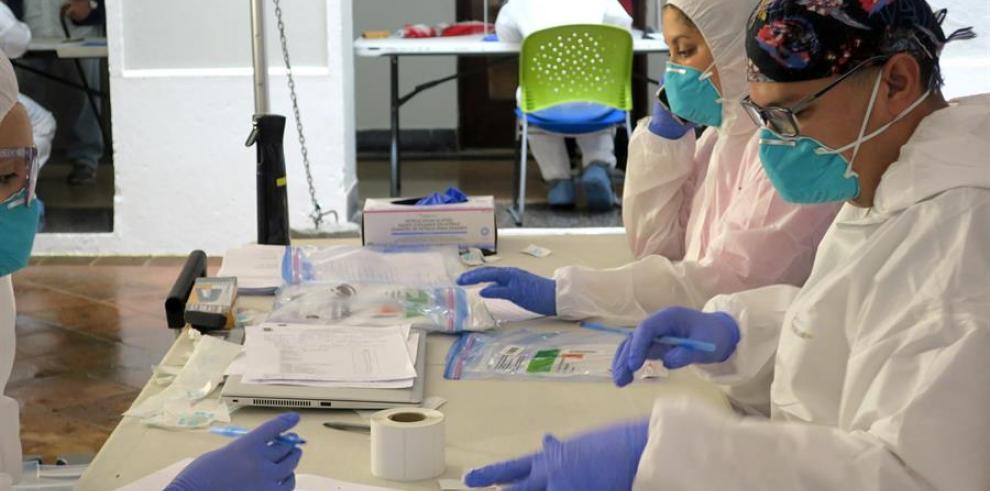 Unos técnicos de laboratorio empaquetan en bolsas de plástico las pruebas del coronavirus realizadas