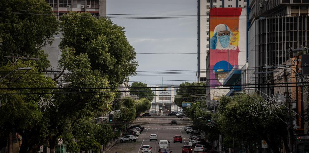 Vehículos circulan por una calle tras el decreto gubernamental de cierre comercial hoy, en Manaos