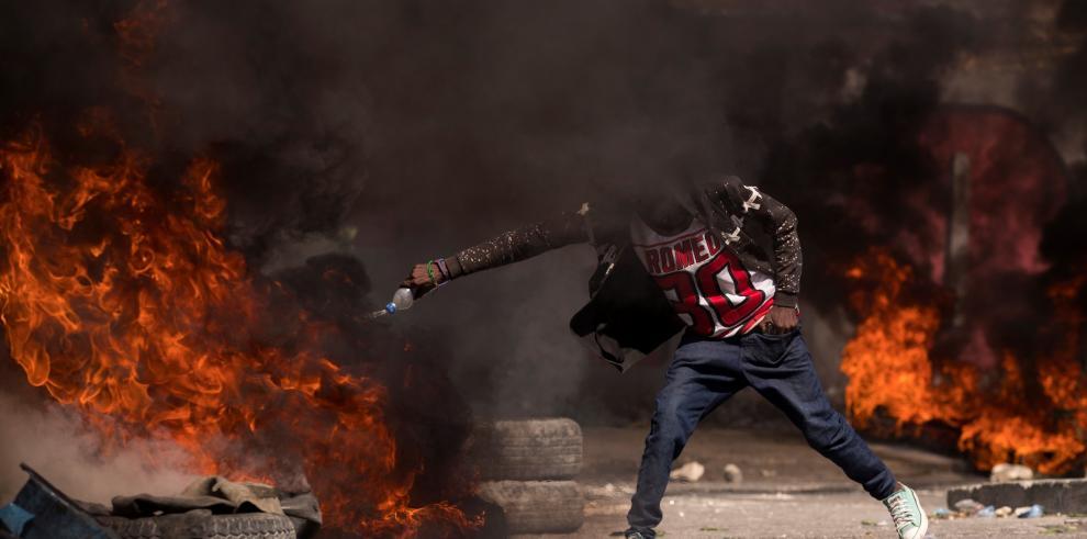 Un manifestante aviva el fuego de una barricada de llantas en llamas durante una protesta
