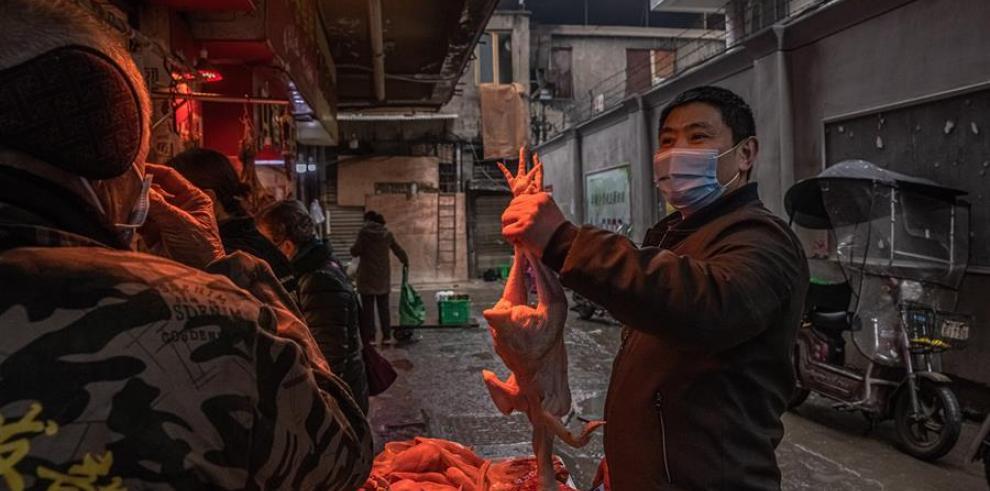 Un hombre con una mascarilla escoge un pollo en el mercado callejero de Wuhan, China.