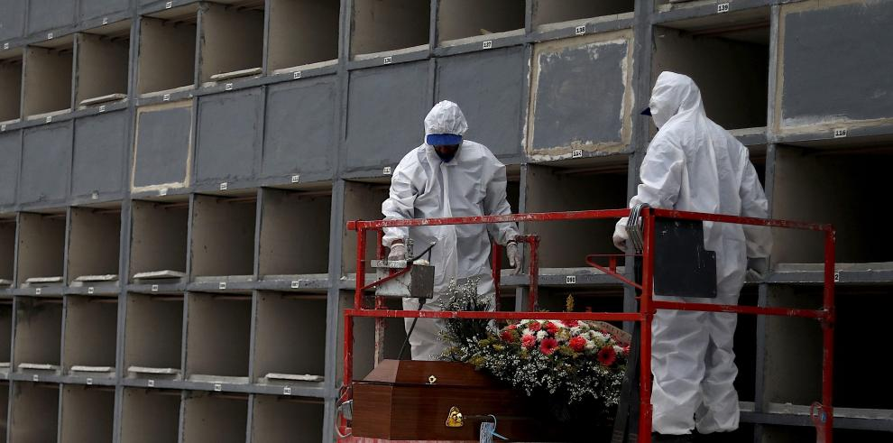 Personal sanitario realizan el entierro de una victima de coronavirus