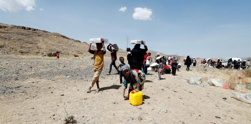 Yemeníes desplazados llevan sus raciones de alimentos proporcionadas por Mona Relief Yemen antes de una conferencia internacional de donantes sobre Yemen