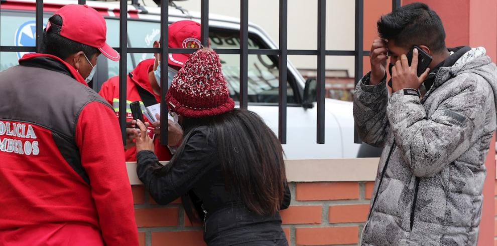 Un bombero habla con una mujer que espera información tras el accidente en el que murieron varios estudiantes hoy, en El Alto (Bolivia).