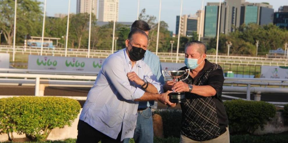 El Dr. Monty Motta entrega la copa del triunfo a Samuel Camarena