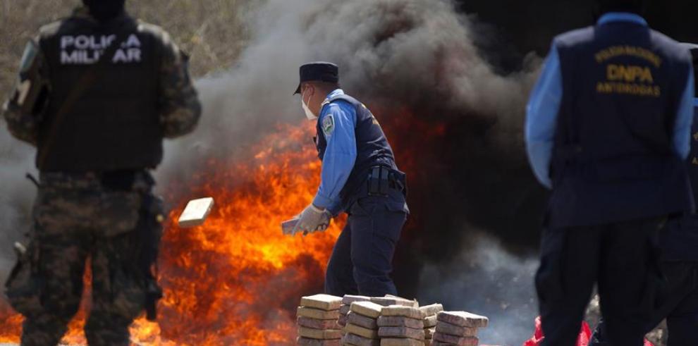 }Un policía hondureño tira un alijo de cocaína a las llamas donde se destruyeron 1426 kilos de droga incautada por las autoridades