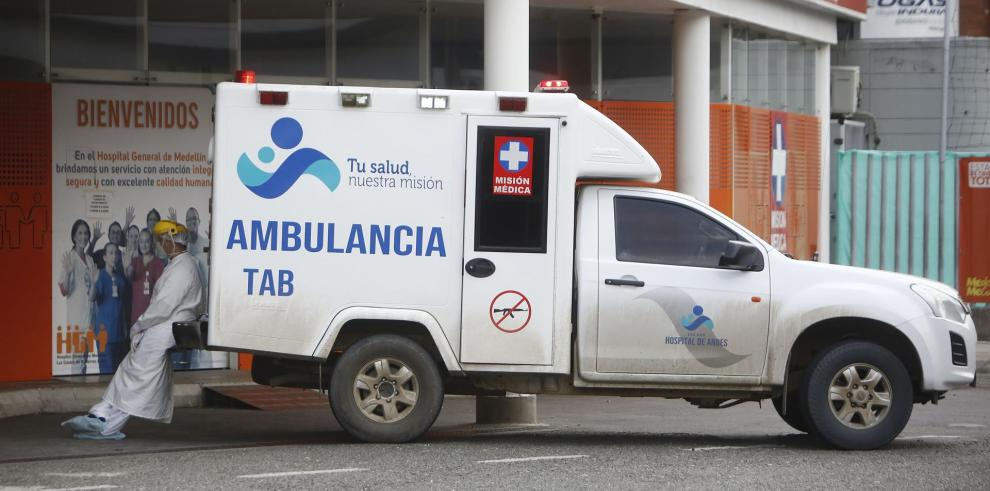 Un trabajador sanitario espera sentado junto a una ambulancia luego de trasladar un paciente covid-19 hoy, en el Hospital General de Medellín