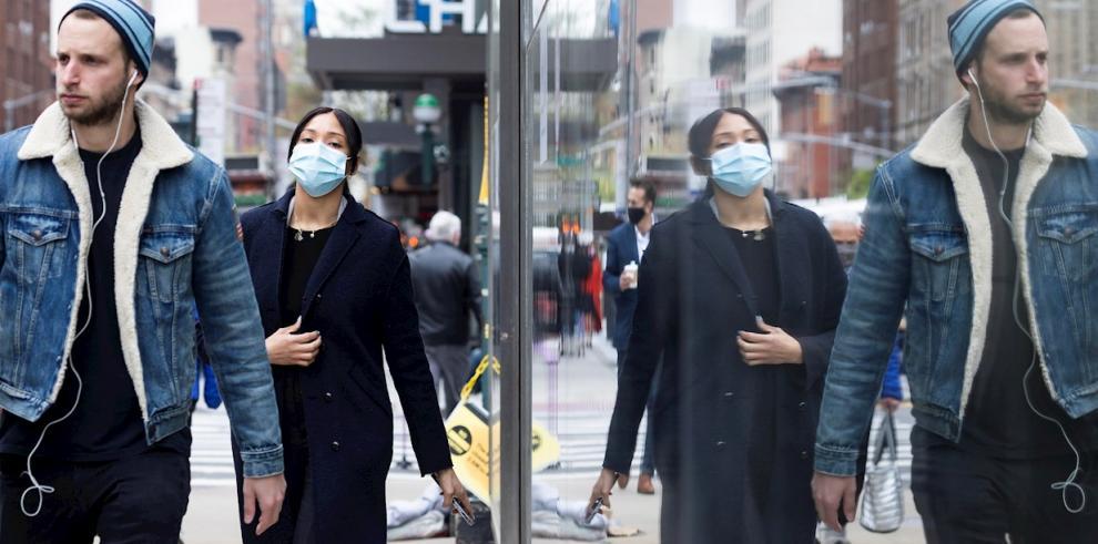 Personas con y sin mascarilla caminan por una calle de Nueva York (EE.UU.), hoy 27 de abril de 2021. EFE/Justin Lane