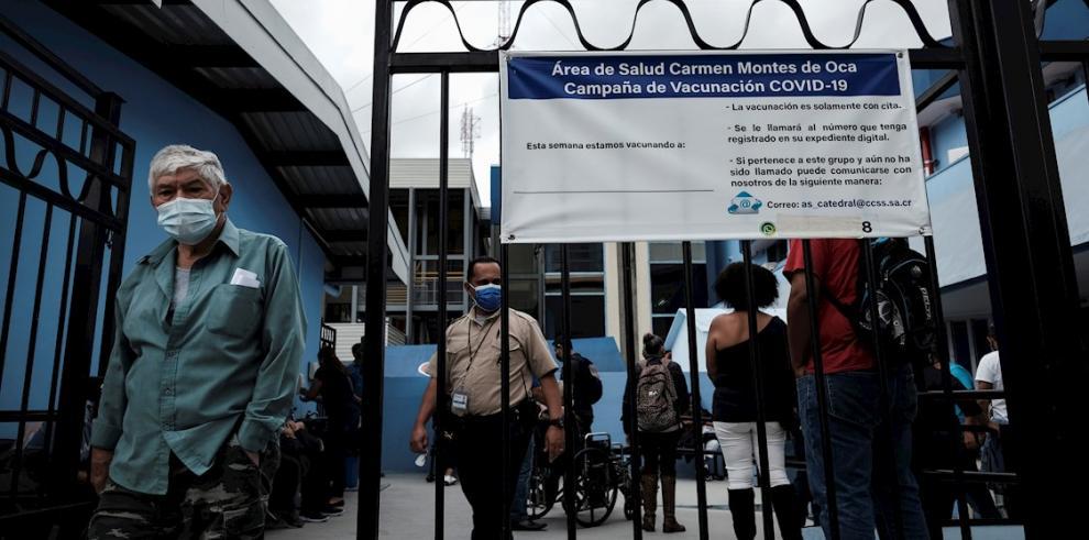Varias personas esperan para ser vacunadas contra la covid-19 en los alrededores del hospital Calderón Guardia