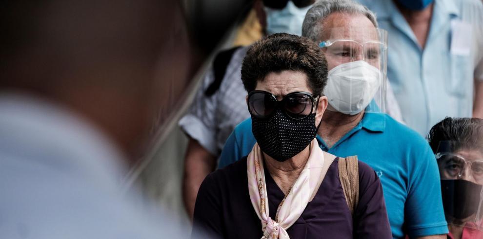 Varias personas esperan para ser vacunadas contra la covid-19, en los alrededores del hospital Calderón Guardia