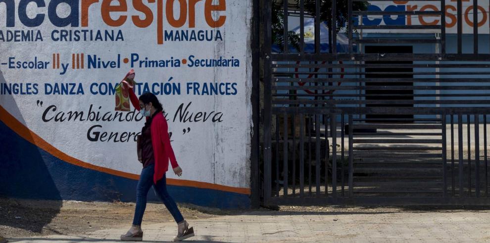 Un mujer camina frente a la puerta cerrada de una escuela