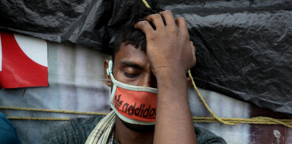 Un trabajador indio descansa mientras espera un tren en la estación de Calcuta.