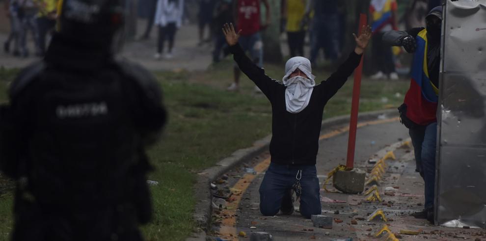 Manifestantes se enfrentan con miembros del Escuadrón Móvil Antidisturbios (ESMAD) durante las protestas ayer en Cali