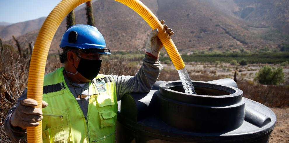 Un trabajador vierte agua potable sobre un tanque de una casa