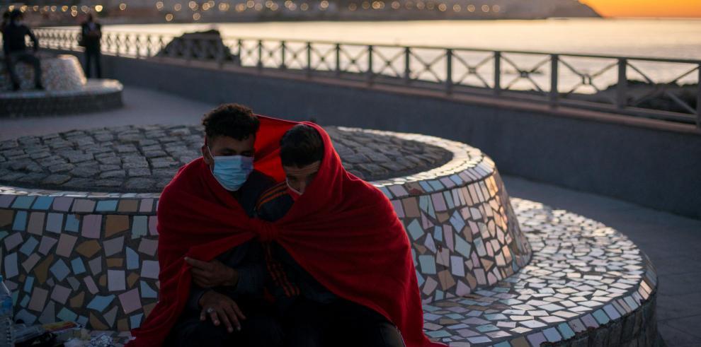 Dos jóvenes inmigrantes se protegen del frío
