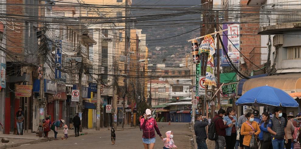 Algunos ciudadanos caminan por una calle comercial durante la jornada de confinamiento en Cochabamba