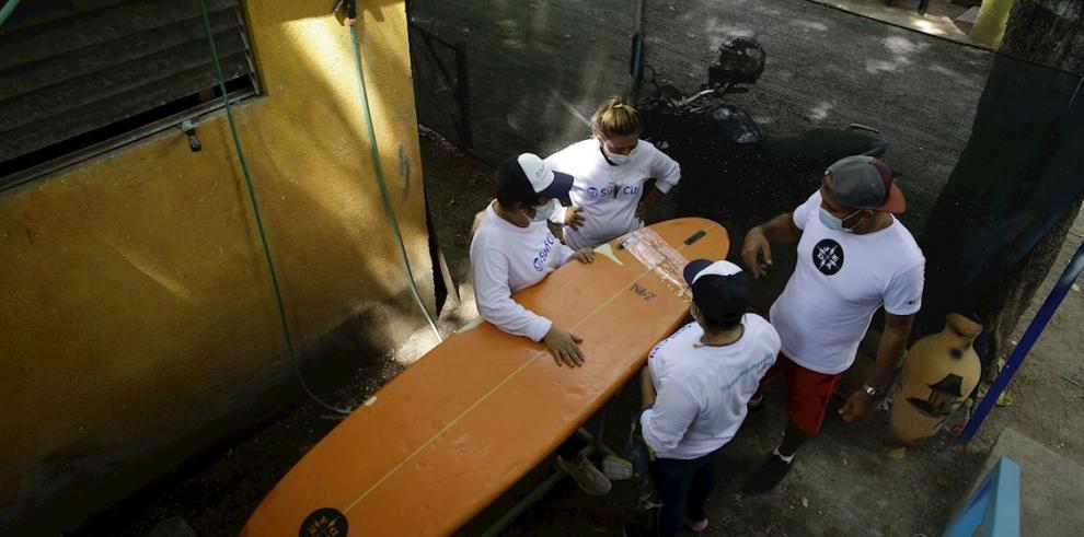 Un instructor capacita a tres mujeres en reparación y fabricación de tablas de surf, el 20 de mayo de 2021 en La Libertad (El Salvador).