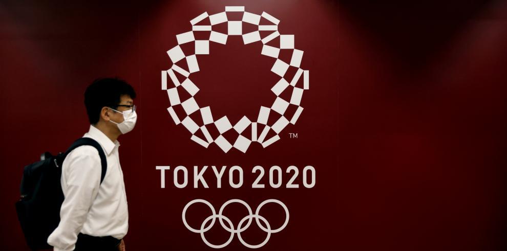 Imagen proveída por ZUMAPRESS de un hombre caminando frente a un anuncio de los Juegos Olímpicos de Tokio 2020.