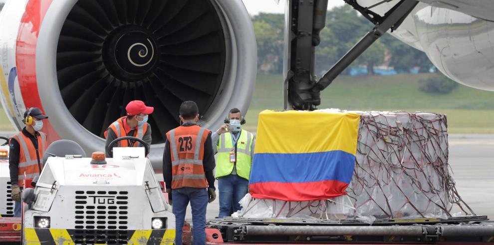 Trabajadores desembarcan un cargamento de vacunas