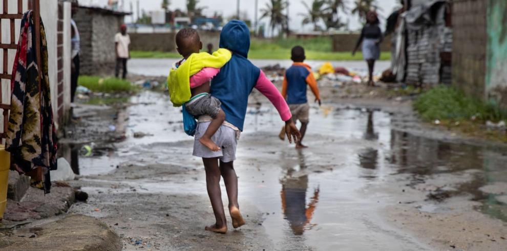 Niños mientras caminan por una calle inundada.