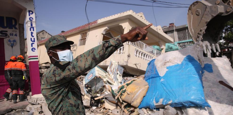 Un soldado haitiano y miembros de la Brigada Internacional de Rescate de Topos trabajan en la búsqueda y rescate de sobrevivientes en una zona afectada por el terremoto de hoy, en Les Cayes
