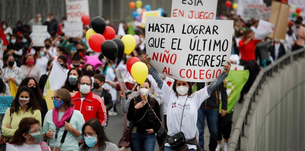 Una mujer sostiene un cartel en una marcha para pedir el regreso a las aulas hoy, en Lima