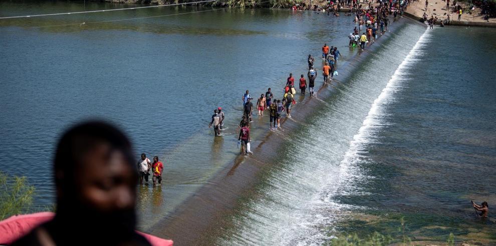Migrantes procedentes de Haití esperan hoy en el río Bravo para cruzar rumbo a Estados Unidos, en Ciudad Acuña, estado de Coahuila (México).