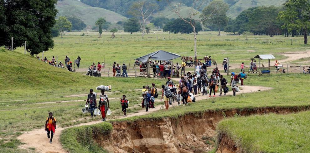 Migrantes haitianos cargan sus pertenencias para instalarse en un campamento donde pasarán la noche para iniciar su viaje hacia el Tapón del Darién.