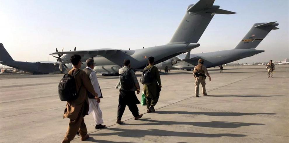 Varias personas estaban esperando su turno para abordar un avión militar en el Aeropuerto Internacional Hamid en Kabul, Afganistán, el 23 de agosto.