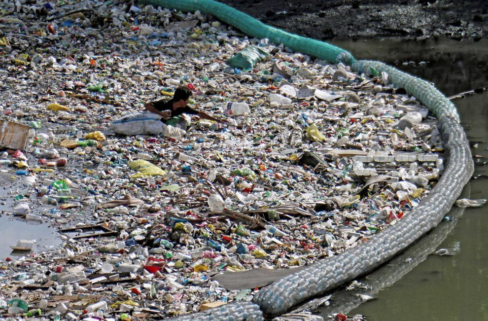 Un hombre recolecta botellas de plástico entre los residuos que una malla impide que alcancen el mar en un río en Cebu (Filipinas)